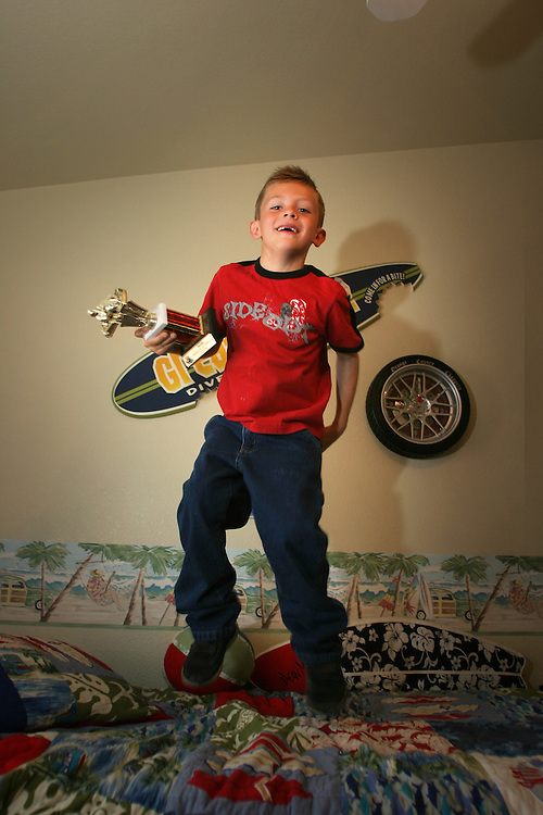 Cruz Fiore (7) in his room at Las Vegas Nevada jumping on his bad with one of his trophies. Monday March. 5, 2007....Cruz is a professional go kart race driver...He weans few competitions in Nevada and California. ..Cruz have a kart that he named ?the willed?, it in zebra colors...