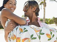 Man carrying woman on beach half length