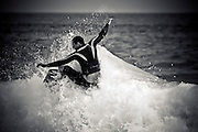 candid black and white capture of body boarder on the crest of a wave with arms outspread