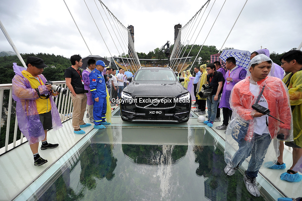 ZHANGJIAJIE, CHINA - JUNE 25:<br /> <br /> A car drives over glass-bottomed bridge for a safety test at Zhangjiajie Grand Canyon on June 25, 2016 in Zhangjiajie, Hunan Province of China. World\'s tallest and longest glass-bottomed bridge has been completed and took a global broadcast through television and internet medias to show its safety. More than thirty citizens and visitors thumped the bridge with hammer in the test event.<br /> &copy;Exclusivepix Media