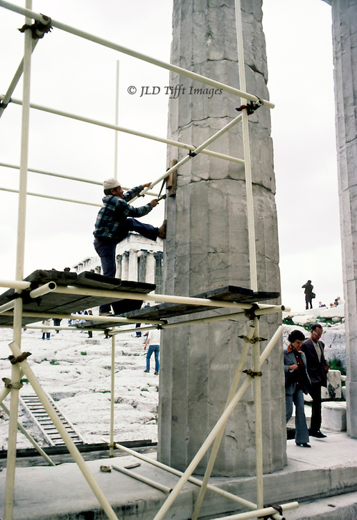 Acropolis, Propylaea, workmen doing repairs with scaffolding and tools.  One on the scaffold of the Propylon tightens a clamp around a column.
