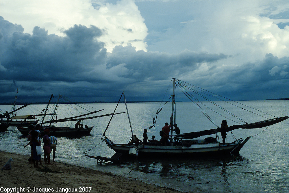Silhouette of fishing boats returning at dusk under cloudy sky, Mosqueiro Island, Amazon estuary, Para, Brazil.