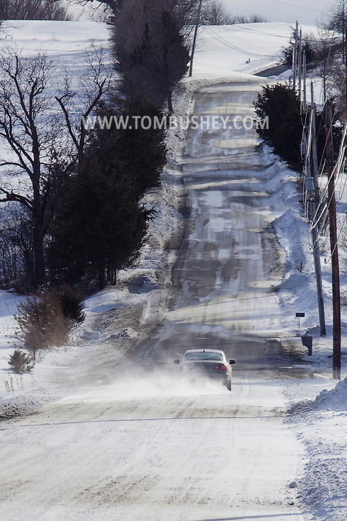 Chester, New York - Strong winds blow snow across Black Meadow Road as a car drive through on Feb. 19, 2015. ©Tom Bushey / The Image Works