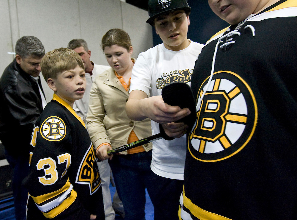 ssc-02cole wn 033109-06.JPG.BOSTON March 31: Cole Pasqualucci, 12 of Scituate, takes in a recent Boston Bruins' game on his birthday with friends in Bruins' center Patrice Bergeron's suite. Pasqualucci suffers from a rare kidney disease and six years ago struck up a friendship with Bergeron during a hospital stay. Pasqualucci's friends (from left) Meg Thibeault, Joey Gaziano and Devin McCarthy examine his newly signed stick from Bergeron. . .Photos by Will Nunnally for the Patriot Ledger.