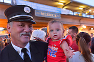 Merrick, New York, USA. September 11, 2015. RILEY E. GIES, one-year-old granddaughter of Fire Chief Ronnie E Gies who died responding to 9/11 NYC Terrorist Attack, is held by CRAIG MALTZ, a Bellmore volunteer firefighter, at Merrick Memorial Ceremony for Merrick volunteer firefighters and residents who died due to 9/11 terrorist attack at NYC Twin Towers. Ex-Chief Ronnie E. Gies  of Merrick F.D. and FDNY Squad 288, and Ex-Captain Brian E. Sweeney, of Merrick F.D. and FDNY Rescue 1, died responding to the attacks on September 11, 2001.