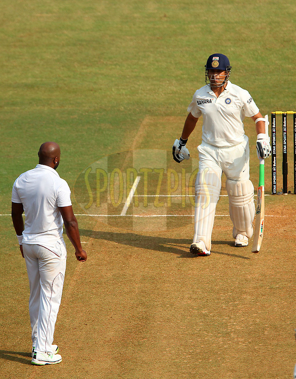 Sachin Tendulkar of India and Tino Best of West Indies  during day two of the second Star Sports test match between India and The West Indies held at The Wankhede Stadium in Mumbai, India on the 15th November 2013<br /> <br /> This test match is the 200th test match for Sachin Tendulkar and his last for India.  After a career spanning more than 24yrs Sachin is retiring from cricket and this test match is his last appearance on the field of play.<br /> <br /> <br /> Photo by: Ron Gaunt - BCCI - SPORTZPICS<br /> <br /> Use of this image is subject to the terms and conditions as outlined by the BCCI. These terms can be found by following this link:<br /> <br /> http://sportzpics.photoshelter.com/gallery/BCCI-Image-Terms/G0000ahUVIIEBQ84/C0000whs75.ajndY