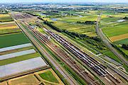 Nederland, Zuid-Holland, Zwijndrecht, 15-07-2012; Kijfhoek, rangeerterrein voor goederentreinen met overzicht van de opstelsporen. Sporen van de HSL buigen af naar rechts. Kijfhoek huisvest Keyrail, exploitant Betuweroute en is in beheer bij ProRail. De Betuweroute, die begint als Havenspoorlijn op de Maasvlakte, verbindt via Kijfhoek de Rotterdamse haven met het achterland. Het rangeeremplacement dient voor het sorteren van goederenwagons waarbij gebruik gemaakt wordt van de zwaartekracht, het 'heuvelen': de wagons worden de heuvel opgeduwd, bij het de heuvel afrollen komen ze, door middel van wissels, op verschillende verdeelsporen. Railremmen zorgen voor het automatisch remmen van de wagons. Na het heuvelproces staan de nieuw samengestelde treinen op aparte opstelsporen..Kijfhoek, railway yard used by ProRail and Keyrail (Betuweroute operator). Kijfhoek connects via the Betuweroute (beginning as Havenspoorlijn on the Maasvlakte), through the port of Rotterdam with the hinterland. The shunting yard for sorting wagons makes use of gravity. The new trains are assembled on separate tracks..luchtfoto (toeslag), aerial photo (additional fee required).foto/photo Siebe Swart