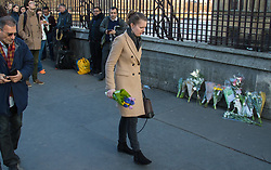 Westminster, London, March 23rd 2017. With Westminster Bridge, scene of Wednesday's terror attack reopened following forensic investigations, members of the public lay flowers.