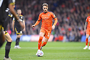 Luton Town player Andrew Shinnie passes the ball downfield in the first half during the EFL Sky Bet League 1 match between Luton Town and AFC Wimbledon at Kenilworth Road, Luton, England on 23 April 2019.