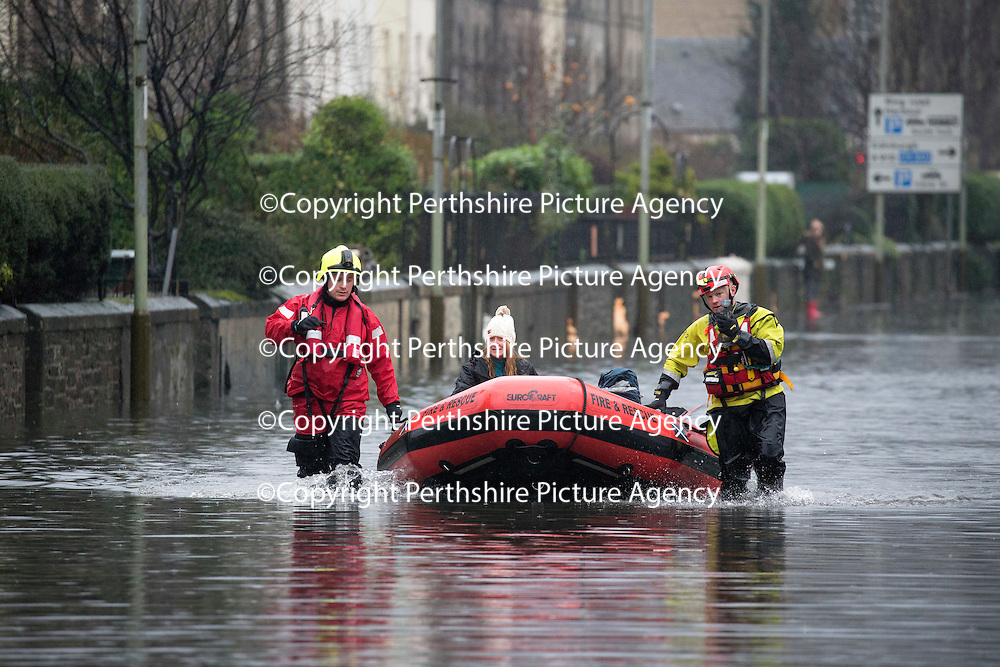 Heavy Rain and More Flooding Continues in Perthshire….05.01.16<br />Marshall Place in Perth was the scene for extensive flooding this morning after continuing rainfall and very high water levels in the nearby River Tay forced the drains to backup leading to widespread floods. A few homeowners opted to be rescued by firefighters with boats, but most opted to stay put.<br />An woman is transported by firefighters on a rescue boat on Marshall Place<br />Picture by Graeme Hart.<br />Copyright Perthshire Picture Agency<br />Tel: 01738 623350  Mobile: 07990 594431