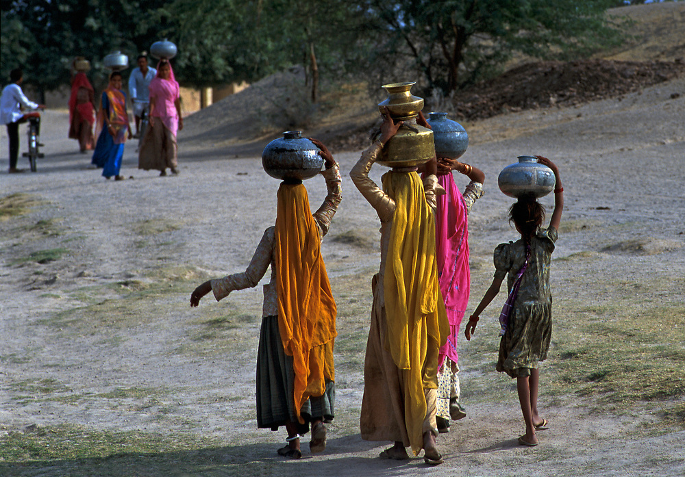 INDIA: Rajasthan<br /> Tribal women collect water in brass jars from the Oasis of Lourdhia, near Jodhpur