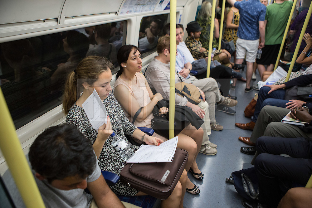 © Licensed to London News Pictures. 01/07/2015. London, UK. A woman fans her self on a morning in which commuters and tourists struggle with the intense heat on the London Underground this morning (01/07) on what is set to be the hottest day this decade. Photo credit : James Gourley/LNP