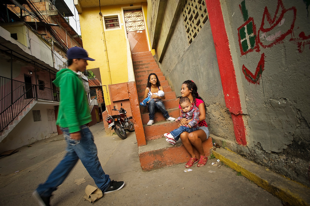 A boy visits sisters Yanaifre and Keisy Acevedo and their babies, Dilan and John in a slum in Caracas, Venezuela.  Both girls got pregnant when they were 15-years old. Venezuela has the highest rate of teenage pregnancies in Latin America.  26 percent of babies are born to underage mothers.
