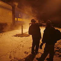 Canada, Alberta, Engineers on VIA Rail train chat in snowstorm at station in Rocky Mountains