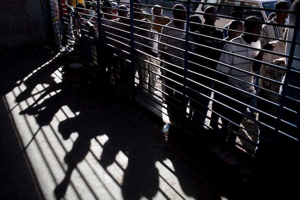 Voters form a line outside a polling station as they wait to cast their ballots in presidential and legislative elections in Port-au-Prince, Haiti.