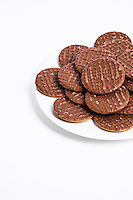 Plate full of chocolate biscuit over white background