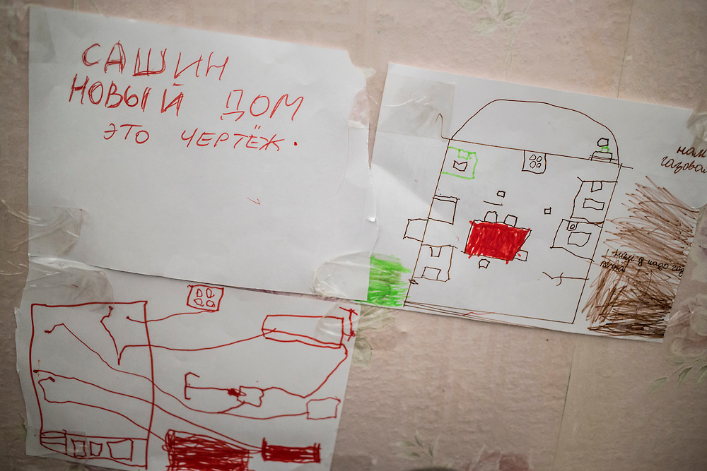 "DNIPRODZERZHINSK, UKRAINE - OCTOBER 11: A child's drawing labeled ""Sasha's new house"" hangs on the wall at the sports school where about 60 people displaced by fighting in Eastern Ukraine live on October 11, 2014 in Dniprodzerzhinsk, Ukraine. The United Nations has registered more than 360,000 people who have been forced to leave their homes due to fighting in the East, though the true number is believed to be much higher.(Photo by Brendan Hoffman/Getty Images) *** Local Caption ***"