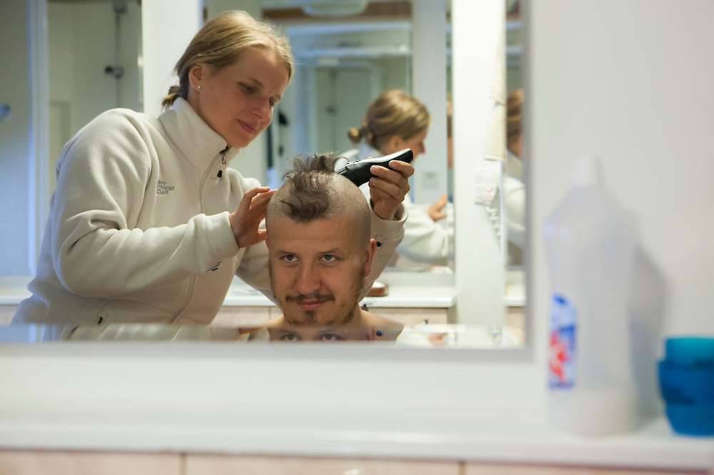 Marta Bania shaves Lukasz Gryglicki's hair into a crazy mohawk hairdo at the Polish Polar Station, Hornsund, Svalbard.