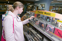 Young woman looking at CDs in a library,