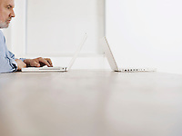 Middle-aged man sitting at desk using laptop another laptop at opposite edge of desk profile