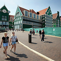 Nederland, Zaandam , 6 juli 2013.<br /> Wandeling door de binnenstad van Zaandam.<br /> Starten bij De Werf aan de Oostzijde. Daarvandaan kun je lopen op een soort boulevard tussen de flats en het water. De eerste stop is De Fabriek, filmhuis en eetcafé met terras aan de Zaan met uitzicht op de sluis. Daarna de sluis zelf.<br /> Dan langs het winkelgebied richting de Koekfabriek: Het oude Verkade pand dat is verbouwd en waar nu de bieb en sportschool en restaurant etc. in zitten.<br /> (Dat is aan de overkant van het startpunt) en misschien nog de Zwaardemaker meepakken aan de Oostzijde. Dat is een oud pakhuis die Rochdale enige jaren geleden heeft verbouwt tot appartementen met een stukje Nieuwbouw.<br /> Ook doen: het Russische buurtje vlakbij de Zaan. Dit jaar staat Rusland in de schijnwerpers en Zaandam heeft een speciale band met Rusland, vanwege het Czaar Peterhuisje en de Russische buurt. <br /> Op de foto: de nieuwe in Zaanse stijl gebouwde woonwijk en winkelcentrum.<br /> Foto:Jean-Pierre Jans