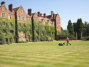 Man mowing grass lawn in courtyard of Selwyn College, University of Cambridge, England