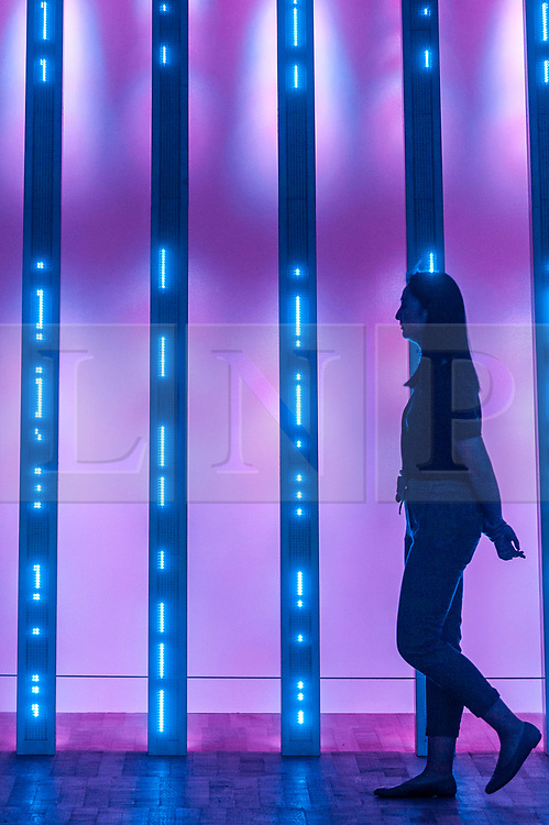 "© Licensed to London News Pictures. 20/07/2018. LONDON, UK. A staff member views ""BLUE PURPLE TILT"", 2007, by Jenny Holzer at the preview of ARTIST ROOMS: Jenny Holzer at Tate Modern. The annual free display includes text-based installations and paintings by the American artist Jenny Holzer and runs 23 July to summer 2019.  Photo credit: Stephen Chung/LNP"