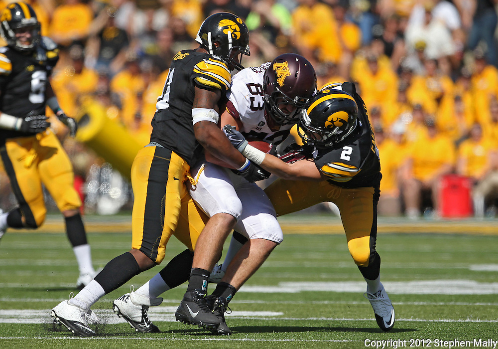 September 29 2012: Minnesota Golden Gophers tight end Drew Goodger (83) is hit by Iowa Hawkeyes linebacker Anthony Hitchens (31) and defensive back Greg Castillo (2) after a catch during the third quarter of the NCAA football game between the Minnesota Golden Gophers and the Iowa Hawkeyes at Kinnick Stadium in Iowa City, Iowa on Saturday September 29, 2012. Iowa defeated Minnesota 31-13 to claim the Floyd of Rosedale Trophy.