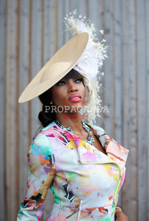 LIVERPOOL, ENGLAND - Friday, April 4, 2014: Lystra Adams from Ghana wearing a hat from Dawn Guibert, outfit from Ted Baker and bag a shoes from Valentino during Ladies' Day on Day Two of the Aintree Grand National Festival at Aintree Racecourse. (Pic by David Rawcliffe/Propaganda)
