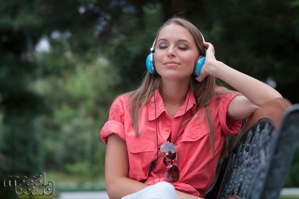 Relaxed young woman listening to headphones on park bench