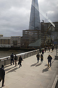 A aerial view of pedestrians crossing London Bridge, beneath the tall Shard tower on the south bank of the Thames river, on 3rd March 2020, in London, England.