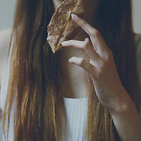 faceless portrait of a young girl holding a dead leaf infront of her