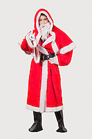 Portrait of young woman in Santa costume gesturing against gray background