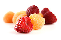 Red and yellow raspberries on white background