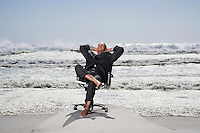 Senior business man sitting on office chair on beach
