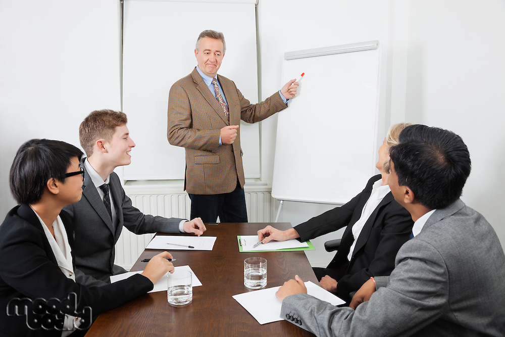 Middle-aged man using whiteboard in business meeting