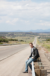 man in a leather jacket sitting on the side of a long road in New Mexico