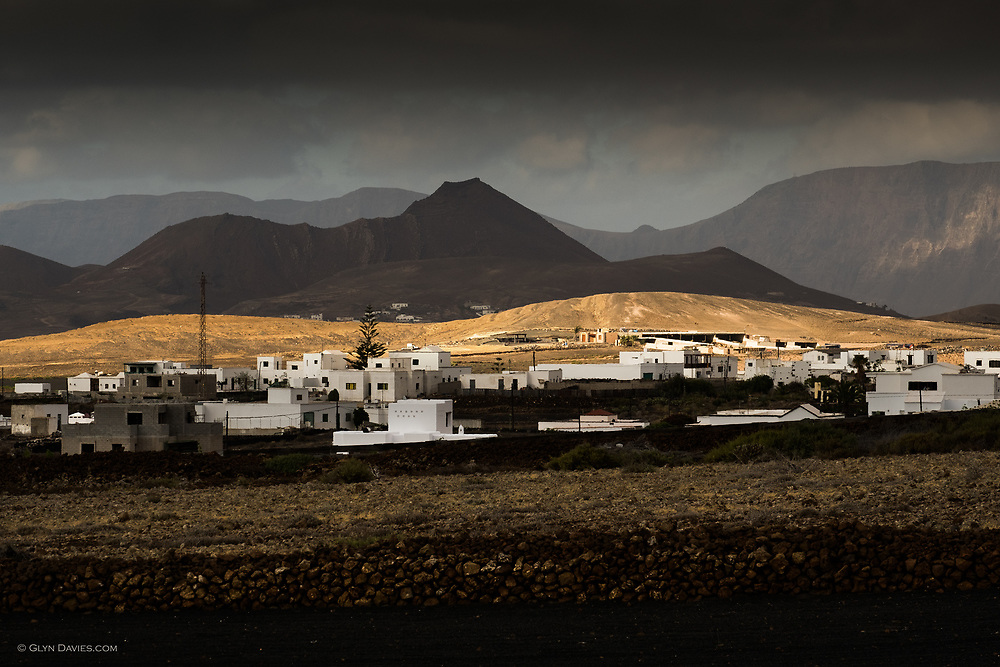 A short burst of sunshine plays across a small hillside near the black-earthed landscape near Tinajo in central Lanzarote. Dark clouds hang over the cliffs of Famara and the clearly volcanic landscape forms the backdrop.