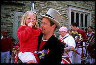 Parade marshall carries little girl in his arms during obby oss parade on May Day in Padstow; Cornwall, England.