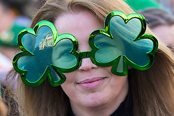 London, March 13th 2016. The annual St Patrick's Day Parade takes place in the Capital with various groups from the Irish community as well as contingents from other ethnicities taking part in a procession from Green Park to Trafalgar Square.  PICTURED: A woman in clover leaf glasses watches the procession. &copy;Paul Davey<br /> FOR LICENCING CONTACT: Paul Davey +44 (0) 7966 016 296 paul@pauldaveycreative.co.uk