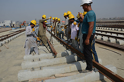 October 4, 2017 - Lahore, Punjab, Pakistan - Chinese engineers busy in work on Orange Line Metro Train at Dera Gujran in Lahore on October 03,2017.One out of 27 sets of orange train reached the Provincial Capital from China and parked at a depot in Dera Gujjran near Ring Road where its official unveiling ceremony is likely to be held on Saturday. As the Punjab government has announced the official launching of metro trains at 27 kilometer track on December 25, the 90 per cent of remaining 26 sets of metro trains are set to arrive here before the inauguration date. (Credit Image: © Rana Sajid Hussain/Pacific Press via ZUMA Wire)