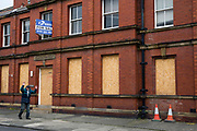 A man walks past (with his hands up) a boarded up and closed down magistrates court, Whitley Bay,  Northumberland. UK. (photo by Andrew Aitchison / In pictures via Getty Images)