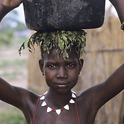 Sudan. Agiep. A young boy walks home after collecting water