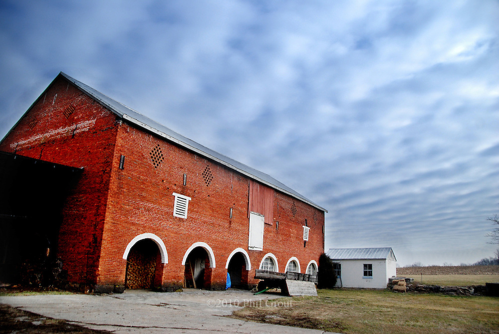 Probably one of the most unusual barns in America is owned by.Matthew and Joanne Pinkas near Silver Run.  The barn is not only.brick-end--it's all brick--all four sides.  It was built in 1825 by.Abraham Hull, a German builder, with bricks used as ship's ballast.for a return voyage from England.  A former dairy farmer, Pinkas.says his cows walked to and from the milking parlor below, through.the unusual six arches.