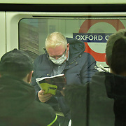 A beggar without mask begging at Oxford Circus underground people sitting inside the tube wearing mask on 21 March 2020, UK.