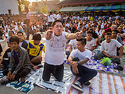 """07 MARCH 2015 - NAKHON CHAI SI, NAKHON PATHOM, THAILAND: A man crawls towards the stage channeling the power of his spiritual tattoo at the Wat Bang Phra tattoo festival. Wat Bang Phra is the best known """"Sak Yant"""" tattoo temple in Thailand. It's located in Nakhon Pathom province, about 40 miles from Bangkok. The tattoos are given with hollow stainless steel needles and are thought to possess magical powers of protection. The tattoos, which are given by Buddhist monks, are popular with soldiers, policeman and gangsters, people who generally live in harm's way. The tattoo must be activated to remain powerful and the annual Wai Khru Ceremony (tattoo festival) at the temple draws thousands of devotees who come to the temple to activate or renew the tattoos. People go into trance like states and then assume the personality of their tattoo, so people with tiger tattoos assume the personality of a tiger, people with monkey tattoos take on the personality of a monkey and so on. In recent years the tattoo festival has become popular with tourists who make the trip to Nakorn Pathom province to see a side of """"exotic"""" Thailand.   PHOTO BY JACK KURTZ"""