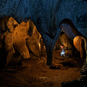 A caver explores the caves of Khao Phraya Phai Rua in Lan Sak, Uthai Thani, Thailand.