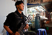 """Sept. 24, 2009 -- PATTANI, THAILAND:  A member of the Thai Rangers, a paramilitary militia trained by the Thai army guard the Pattani night market in Pattani, Thailand. Thailand's three southern most provinces; Yala, Pattani and Narathiwat are often called """"restive"""" and a decades long Muslim insurgency has gained traction recently. Nearly 4,000 people have been killed since 2004. The three southern provinces are under emergency control and there are more than 60,000 Thai military, police and paramilitary militia forces trying to keep the peace battling insurgents who favor car bombs and assassination.   Photo by Jack Kurtz / ZUMA Press"""