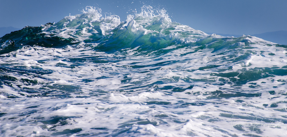 Out in mountainous seas on Monterey Bay, California.  The swelling ocean waves rise to the sky.