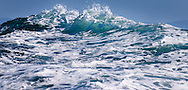 Viewed from a ship in the mountainous seas on Monterey Bay, California, the swelling ocean waves rise to the sky.